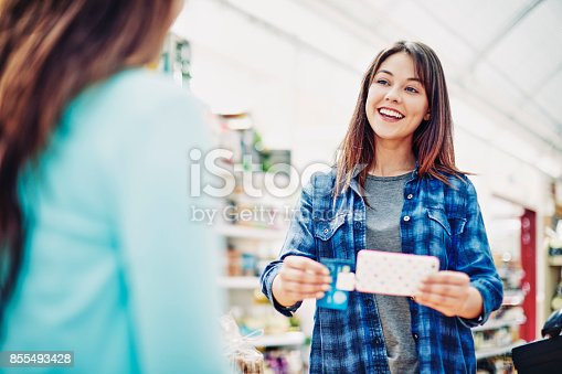 istock Cheerful deli owner receiving payment through credit card from customer 855493428