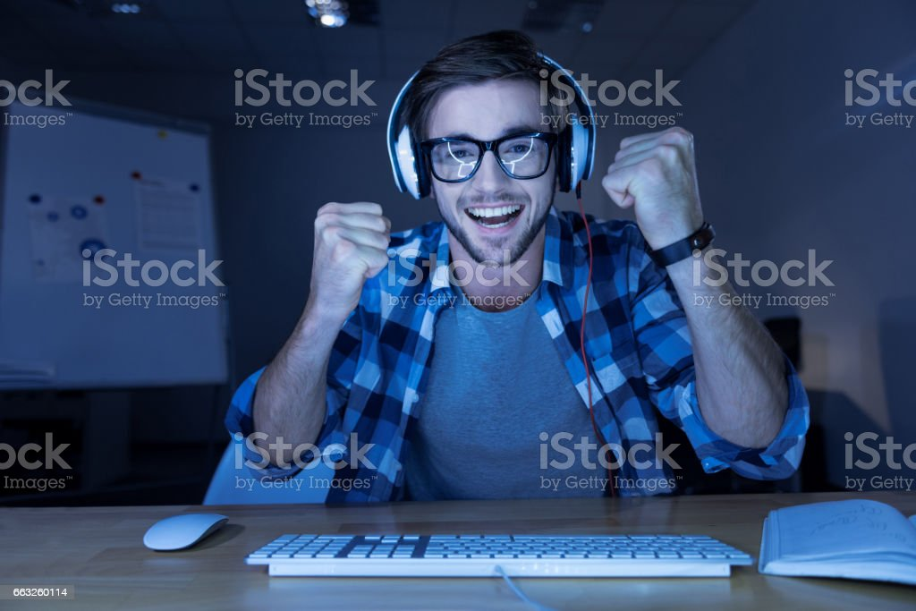 Cheerful delighted man winning the computer game stock photo