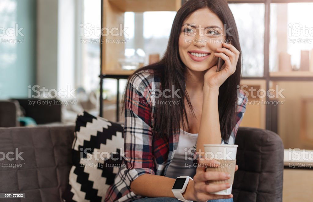 Cheerful delighted woman speaking on the phone