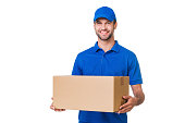 Happy young courier holding a cardboard box and smiling while standing against white background