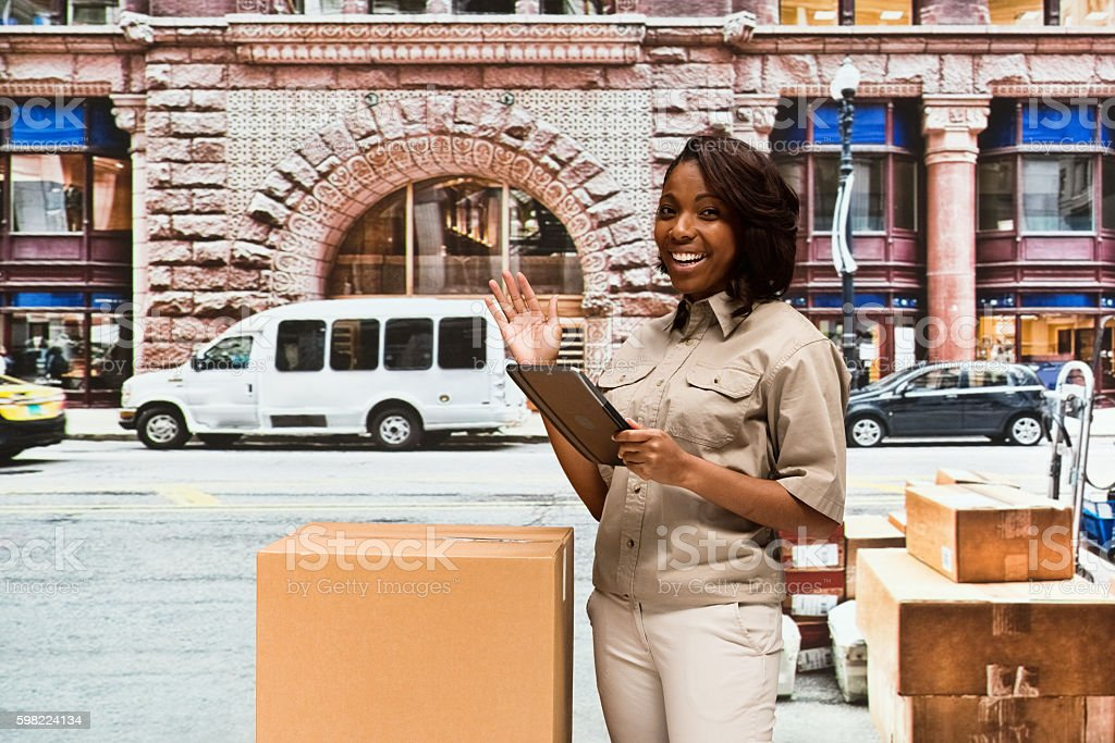 Cheerful delivery person using tablet outdoors foto royalty-free