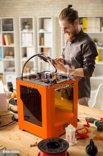 886646936 istock photo Cheerful Designer Working with 3D Printer 886646990
