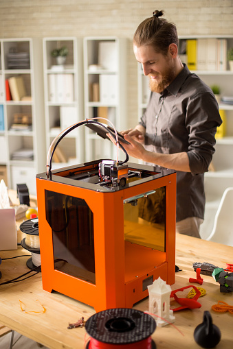 1133176165 istock photo Cheerful Designer Working with 3D Printer 886646990