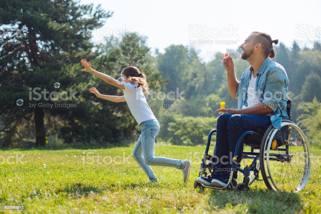 Alegre con discapacidad padre e hija jugando con pompas de jabón - foto de stock