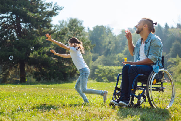 cheerful disabled father and daughter playing with soap bubbles - wheelchair sports stock photos and pictures