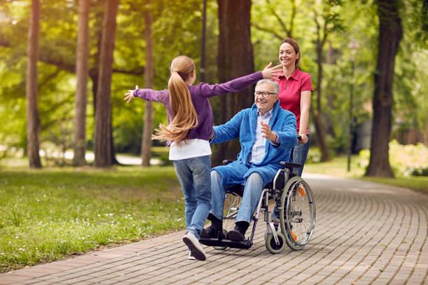 fröhliche deaktiviert großvater im rollstuhl begrüßen seine enkelin - hospiz stock-fotos und bilder