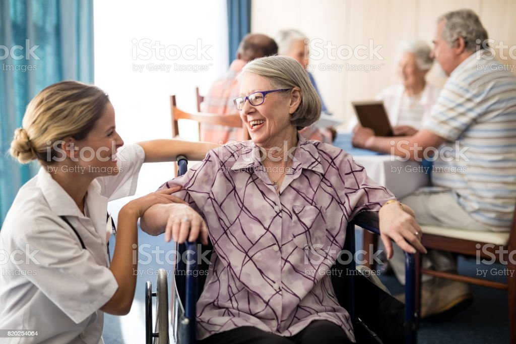 Cheerful disabled senior woman sitting on wheelchair looking at female doctor stock photo