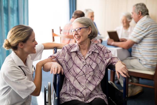 Femme senior handicapée joyeuse, assis sur le fauteuil en regardant femme médecin - Photo
