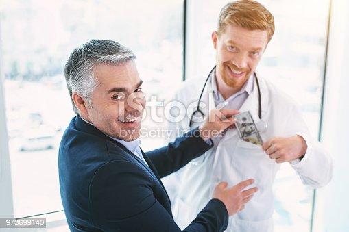 182362845 istock photo Cheerful dishonest doctor taking a bribe 973699140