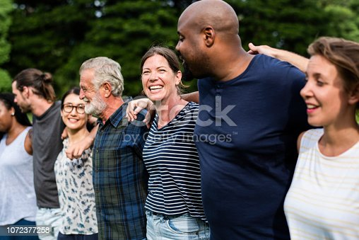 1094812112 istock photo Cheerful diverse people together in the park 1072377258
