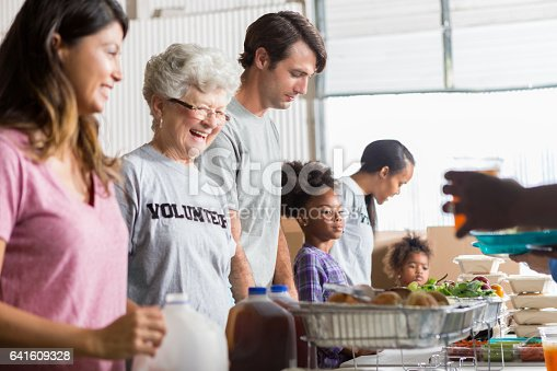 Beautiful senior Caucasian woman smiles while serving others in soup kitchen. She is wearing a volunteer t-shirt and has gray hair. A young mom with her daughters are in the background.