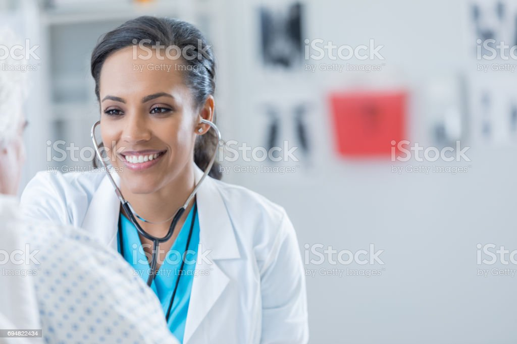 Cheerful doctor examines senior man stock photo