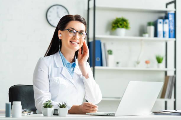 médico alegre en los auriculares que tienen consulta en línea con el paciente en la computadora portátil en la oficina de la clínica - foto de stock
