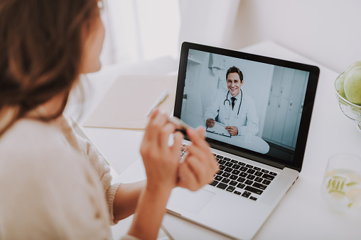 istock Cheerful doctor making video-call to his patient at home 1125882058