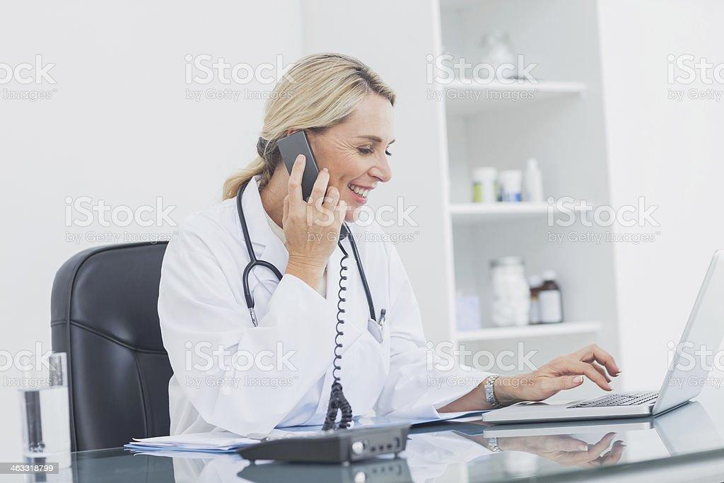 Fröhlich Arzt am Telefon in Ihrem Büro Lizenzfreies stock-foto
