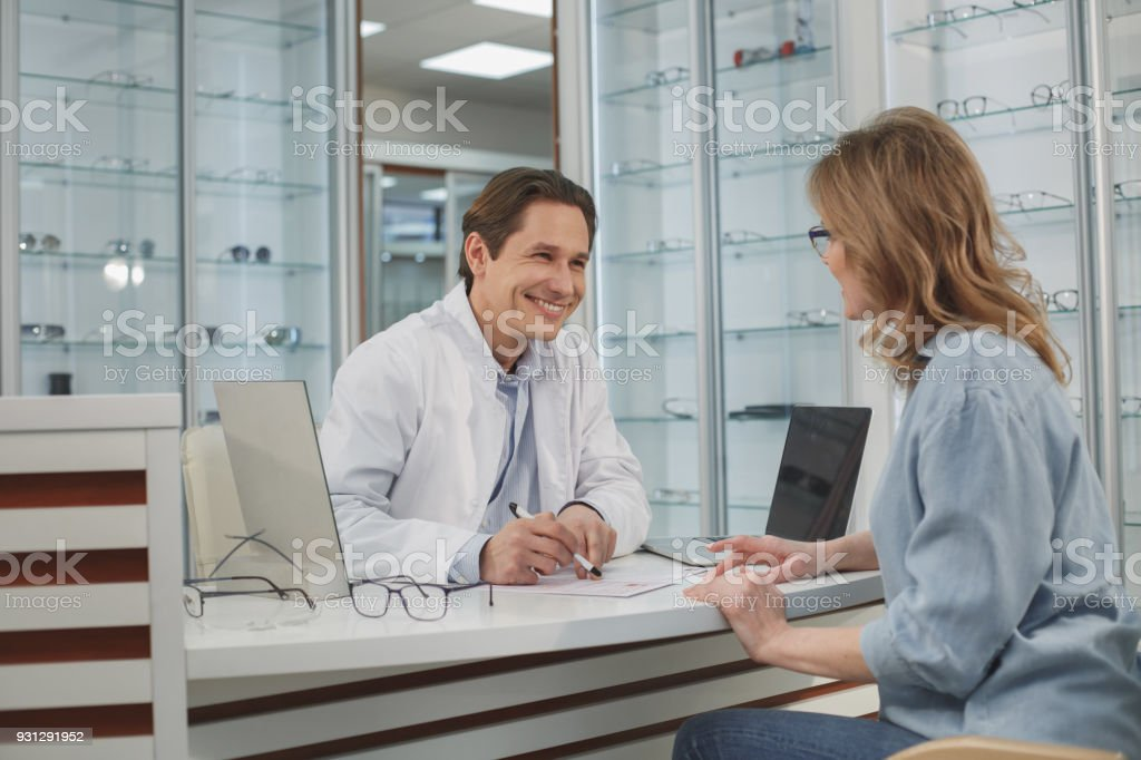 Cheerful doctor speaking with client stock photo
