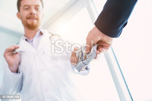 182362845 istock photo Cheerful doctor taking a bribe 973698768