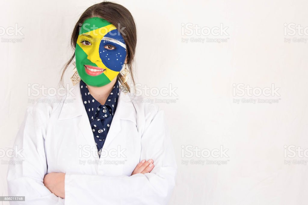 Cheerful  doctor woman with crossed hands and Brazil flag painted on her face stock photo