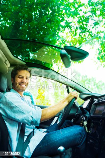 1051147634 istock photo Cheerful driver in his car 155439552