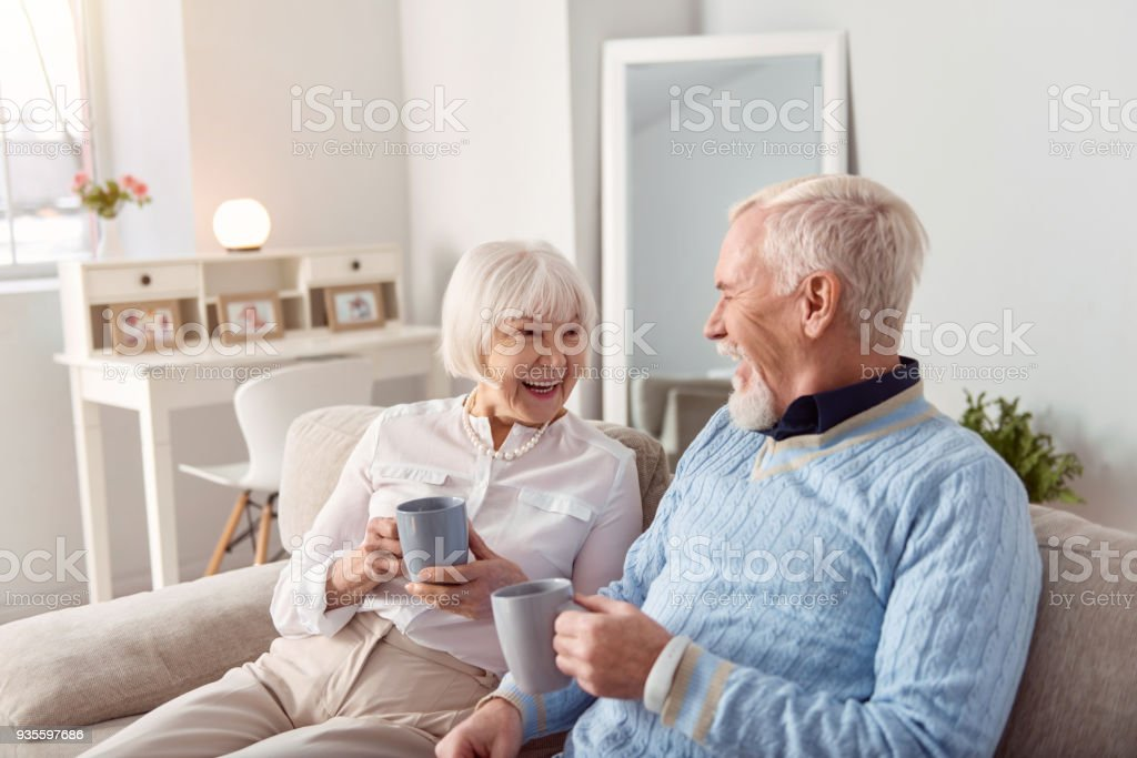 Cheerful elderly couple chatting while drinking coffee stock photo