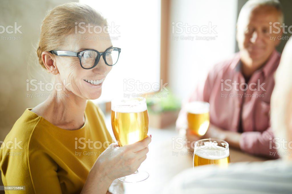 Cheerful elderly lady with beer glass