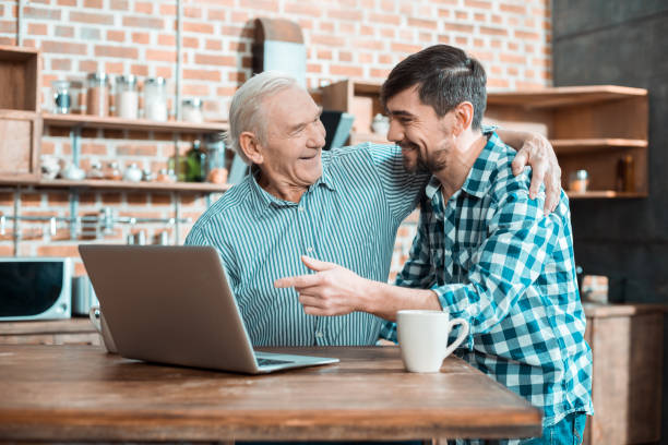 cheerful elderly man hugging his son - baby boomers stock pictures, royalty-free photos & images