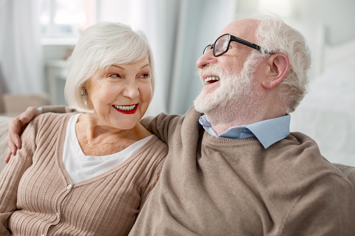 Elderly couple. Cheerful elderly man sitting together with his wife while hugging her