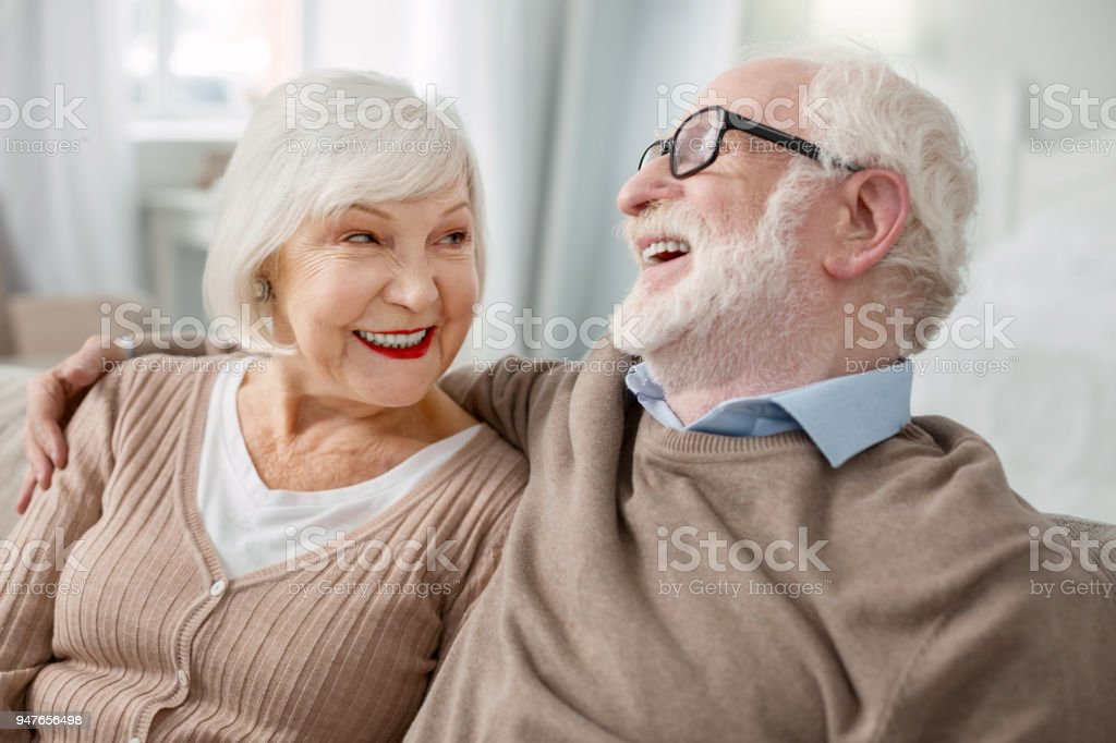 Cheerful elderly man hugging his wife стоковое фото