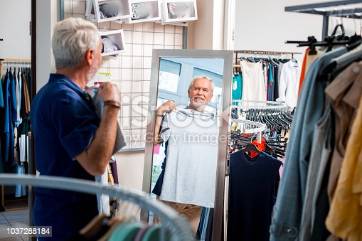 istock Cheerful elderly man looking at the mirror of shopping store 1037288184