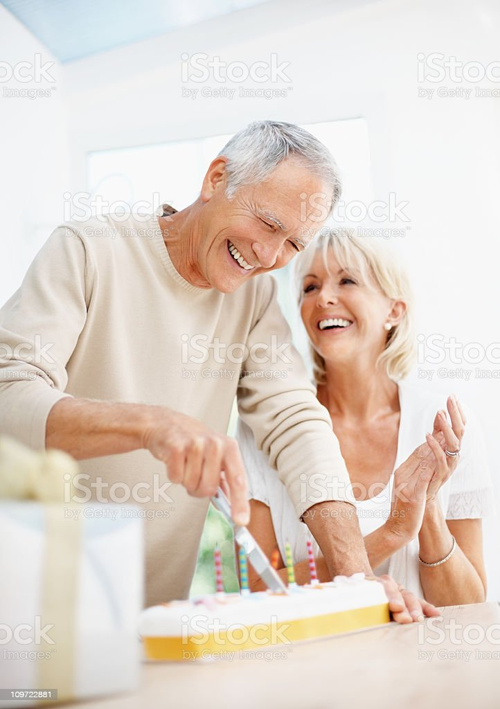Cheerful elderly man with mature woman cutting the cake royalty-free stock photo