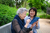 Caring daughter or mature female volunteer teaching her elderly mother or an older woman how to use a tablet. Two women sit on a bench in city park.