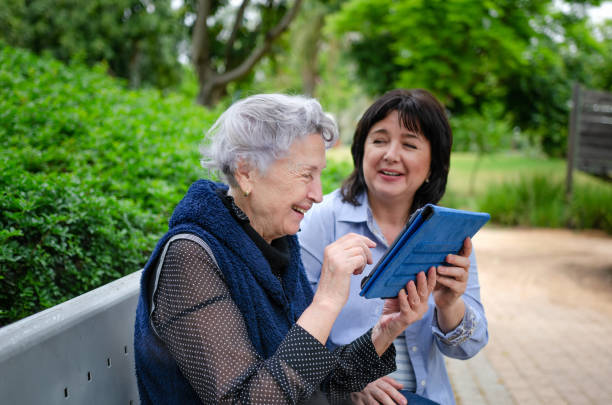 Cheerful elderly woman quickly studies to use the tablet to communicate in social networks stock photo