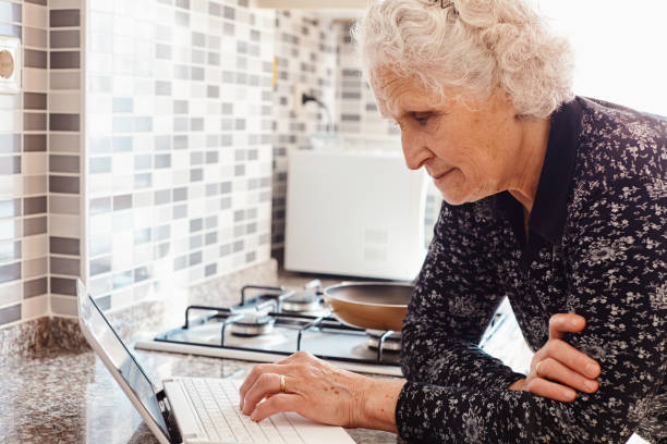 Cheerful elderly woman searching for new recipes with laptop computer on kitchen counter stock photo