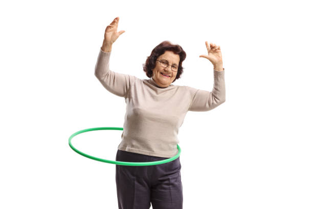 fröhliche ältere frau mit einem hula-hoop - hula hoop workout stock-fotos und bilder