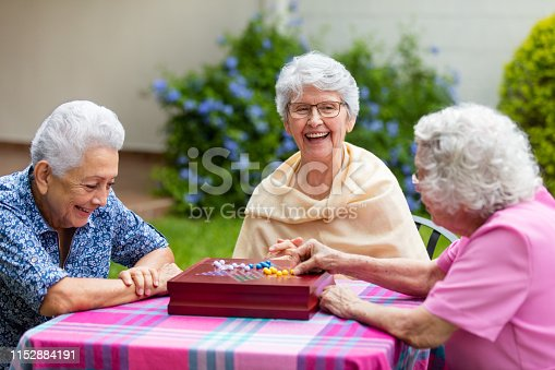 Cheerful latin elderly women sitting at a table outside, playing a boardgame and smiling at each other.