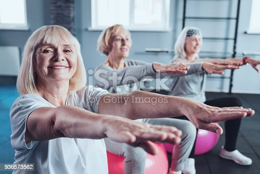 936573360 istock photo Cheerful elderly women stretching hands at fitness club 936573562