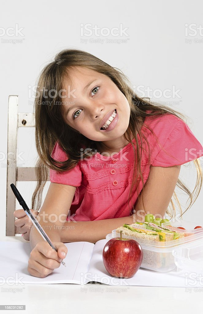 Cheerful elementary school girl does her homework royalty-free stock photo