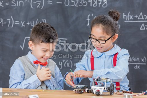 1016655140 istock photo Cheerful elementary STEM students work on robotics project 646729760