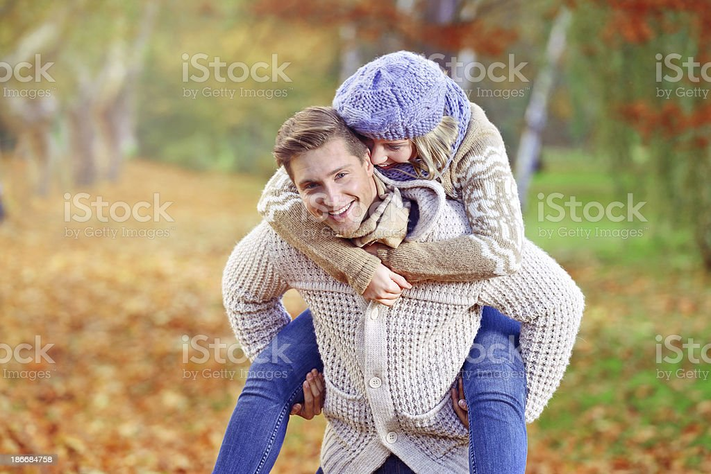 Cheerful enjoying couple in an autumn day at park royalty-free stock photo