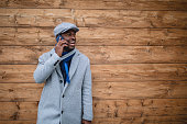 Cheerful entrepreneur talking on a mobile phone by a wood wall