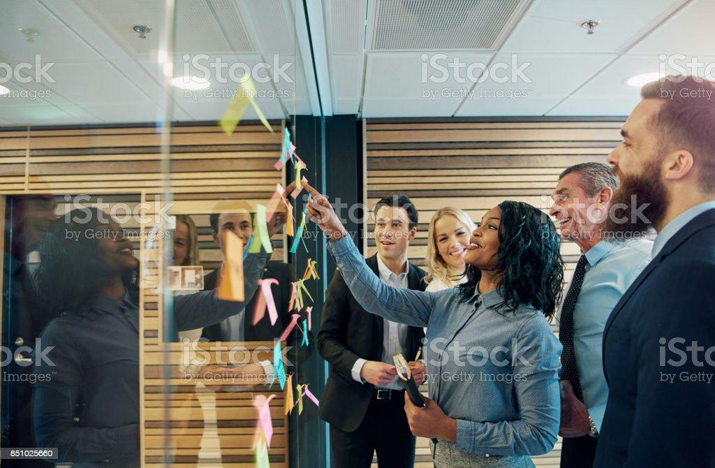 Equipo de empresario alegre hablando en la oficina - foto de stock