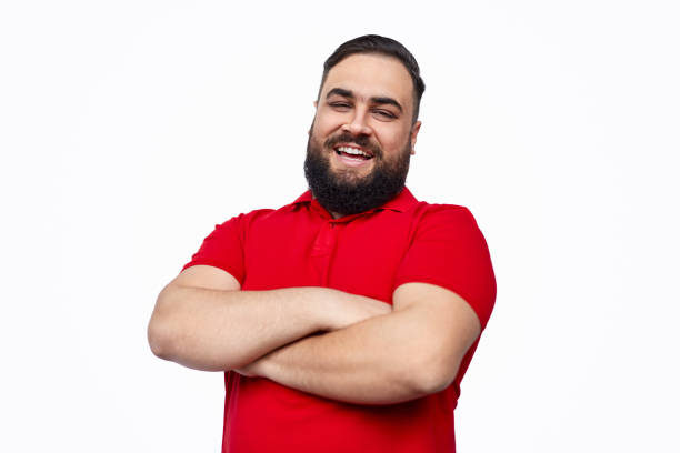 Cheerful ethnic male with folded arms Plus size bearded ethic man in red T-shirt keeping arms crossed and cheerfully smiling for camera while standing against white background red shirt stock pictures, royalty-free photos & images