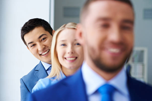 Cheerful ethnic man in row with coworkers stock photo