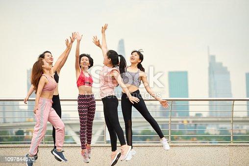 670054434istockphoto Cheerful ethnic sportswomen giving high five 1097844570