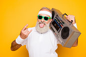 istock Cheerful excited aged funny active sexy athlete cool pensioner grandpa in eyewear with bass clipping ghetto blaster recorder. Old school, swag, sticking tongue, fooling, gym, workout, technology 928017890