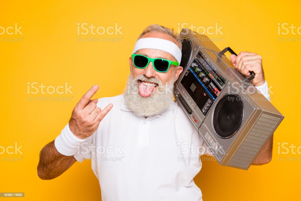 Cheerful excited aged funny active sexy athlete cool pensioner grandpa in eyewear with bass clipping ghetto blaster recorder. Old school, swag, sticking tongue, fooling, gym, workout, technology stock photo