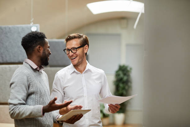 Cheerful excited young colleagues standing in modern office and shrugging shoulders while coming to common decision stock photo