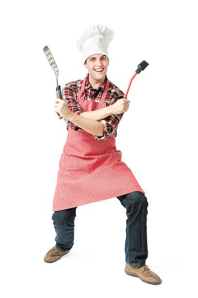 freudig aufgeregt junge grill-koch kochen posieren auf weißem hintergrund - grillschürze stock-fotos und bilder