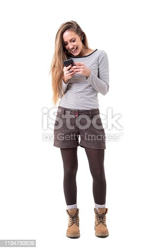 Cheerful excited young stylish woman typing or reading messages on mobile phone. Full body isolated on white background.