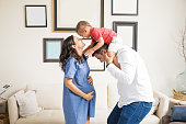Cheerful expectant couple playing with son in living room at home